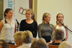 Vier Schülerinnen rezitieren vor dem Publikum.