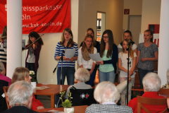 Lesung mehrerer Schülerinnen im Seniorenheim vor Senioren im Publikum.