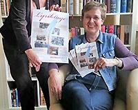 Sabine Post und Karin Gehlen-Düring präsentieren ein Plakat der Lyriktage vor einer Bücherwand.